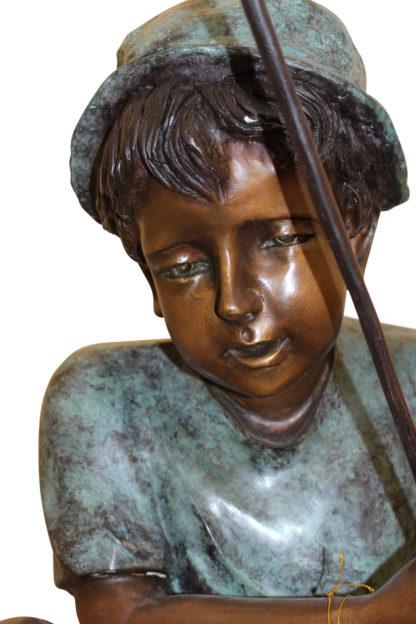 "Boy Sitting on a Tree and Fishing Bronze Statue -  Size: 36""L x 21""W x 37""H."