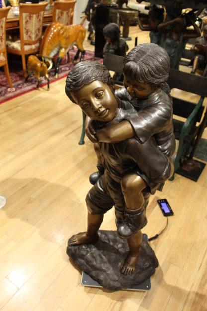 "Boy Giving Girl Piggyback Ride Bronze Statue -  Size: 23""L x 16""W x 46""H."